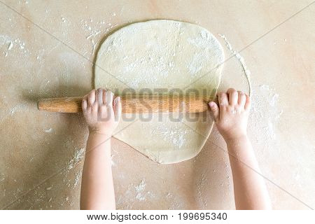 Top view shoot of children's hands rolled dough with a rolling pin on the table