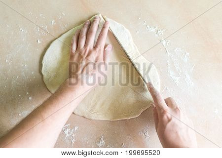 Top view shoot of men's hands cutting raw dough on the table
