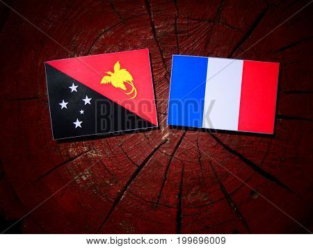 Papua New Guinea Flag With French Flag On A Tree Stump Isolated