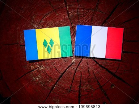 Saint Vincent And The Grenadines Flag With French Flag On A Tree Stump Isolated