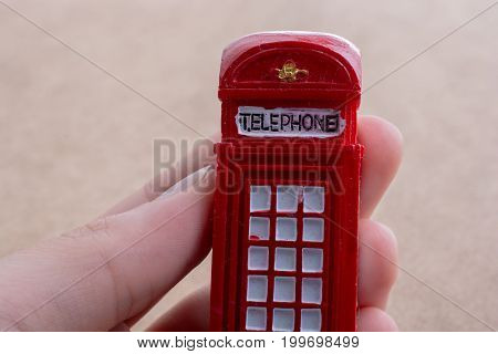 Hand Holding A Red Phone Booth