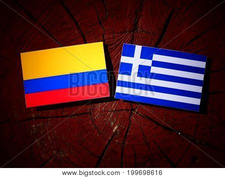 Colombian Flag With Greek Flag On A Tree Stump Isolated
