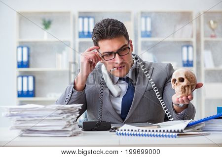 Businessman in the office smoking holding human skull