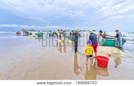 Mui Ne, Vietnam - December 4th, 2016: Fishermen are doing work ominous fishing nets as a way of living daily in the coastal fishing village. This is hard work but feed many families in Mui Ne, Vietnam
