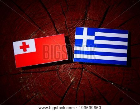 Tonga Flag With Greek Flag On A Tree Stump Isolated