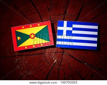 Grenada Flag With Greek Flag On A Tree Stump Isolated