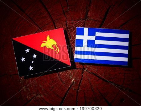 Papua New Guinea Flag With Greek Flag On A Tree Stump Isolated