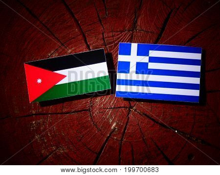 Jordanian Flag With Greek Flag On A Tree Stump Isolated