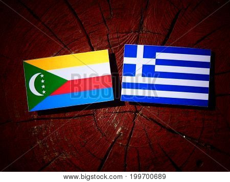 Comoros Flag With Greek Flag On A Tree Stump Isolated