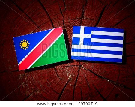 Namibian Flag With Greek Flag On A Tree Stump Isolated