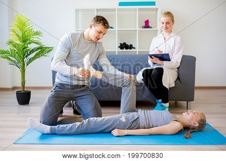 Physiotherapist working with a kid in a clinic