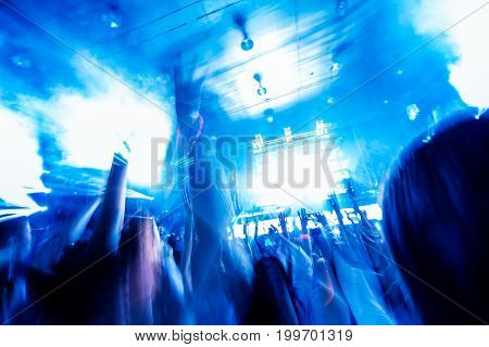 Picture of concert, music festival,party in nightclub, dance floor, disco club, many people standing with raised hands up. Blurred motion in night light rays.