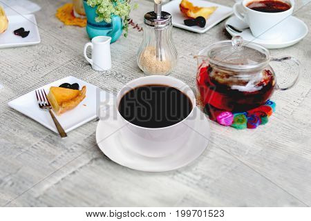 Coffee espresso in white cup and tea in jar with apple pie on a white wooden table.