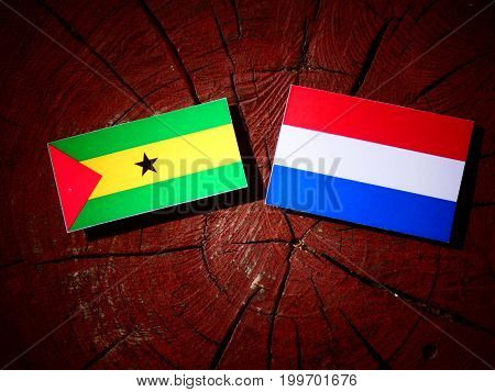 Sao Tome And Principe Flag With Dutch Flag On A Tree Stump Isolated