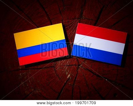 Colombian Flag With Dutch Flag On A Tree Stump Isolated