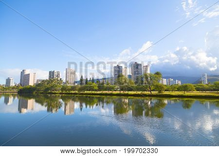 The picturesque panorama of Waikiki suburbs framed by the mirror-like canal surface green golf course and distant mountains. The view of Ala Wai Canal in Waikiki resort area Honolulu Hawaii.