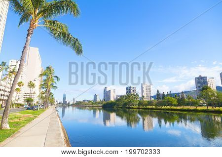 The picturesque panorama of Waikiki suburbs along the canal with reflections Honolulu Hawaii USA. A promenade near the canal with palm trees.