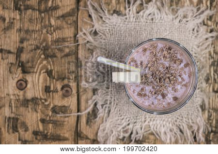 Top view on Cup of chocolate smoothie with a banana on a piece of burlap. The concept of healthy sports nutrition.