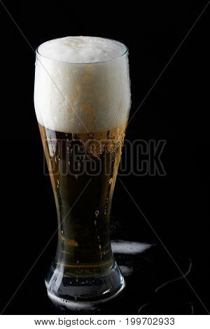 Glass full with beer stand on black background