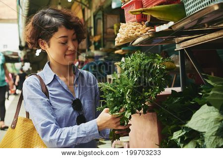 Asian young woman buying bunch of greenery at food market