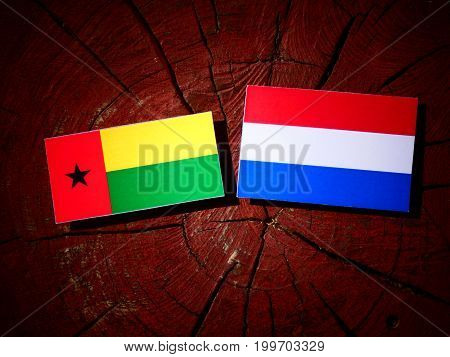 Guinea Bissau Flag With Dutch Flag On A Tree Stump Isolated
