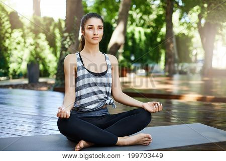 Young fit woman having yoga practice in the morning sitting on a mat in the temple looking off camera