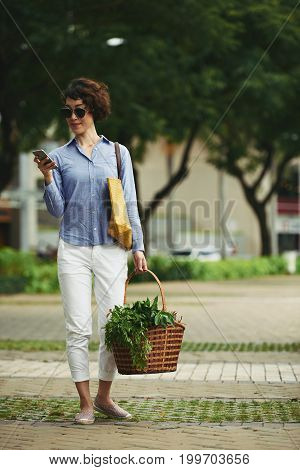 Smiling woman with basket of groceries reading message in smartphone