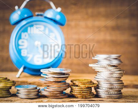 Closeup coins stacked on each other in different positions with alarm clock and wooden background.. Money saving concept.