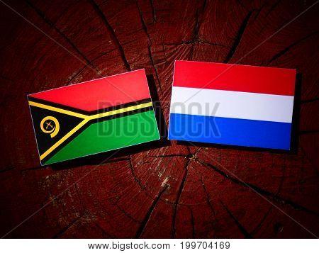 Vanuatu Flag With Dutch Flag On A Tree Stump Isolated