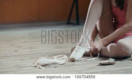 Girl balerina dancer putting on her ballet shoes, close up