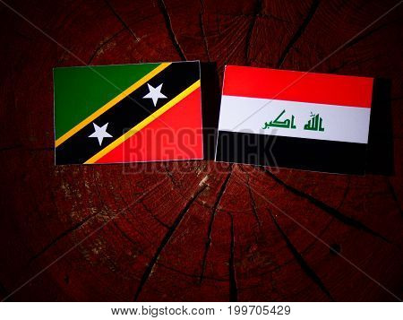 Saint Kitts And Nevis Flag With Iraqi Flag On A Tree Stump Isolated