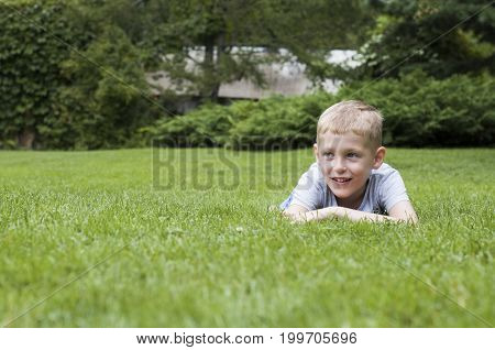 Smiling Kid On A Green Grass