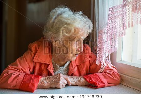 An elderly woman looks out the window of the house.