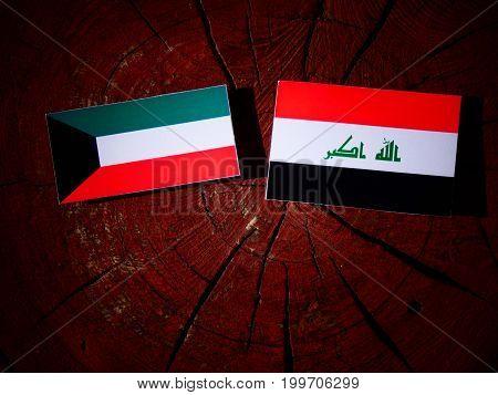 Kuwaiti Flag With Iraqi Flag On A Tree Stump Isolated