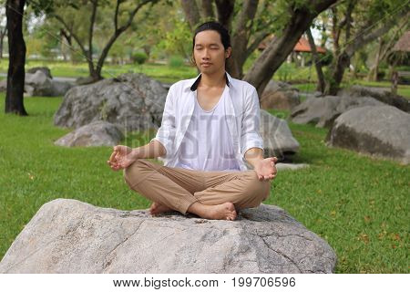 Portrait of young yogi man in white shirt doing yoga meditation while sitting in lotus position on the rock in beautiful outdoor park.