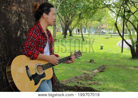 Portrait of young guitarist standing against a tree and playing acoustic guitar in beautiful nature background.