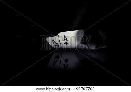Holding 2 Aces On Black Background