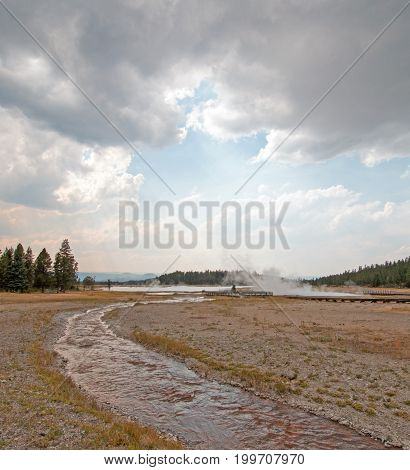 Tangled Creek running into Hot Lake under cumulus cloudscape in the Lower Geyser Basin in Yellowstone National Park in Wyoming USA