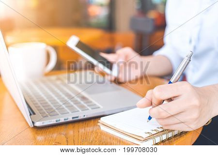 The Hand Of A Business Woman Writing With A Pen In Notepad And Working On A Mobile Phone In The Offi