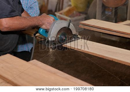 Side view of electric circular saw is being cut a piece of wood against hands of senior carpenter in carpentry workshop.