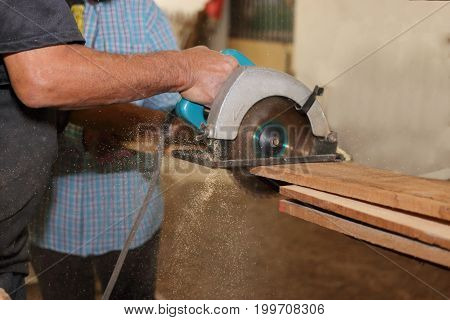Electric circular saw is being sawed with a piece of wood by a senior carpenter in carpentry workshop.