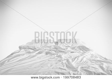 unmade bed with crumpled bed sheet, a blanket and pillows after comfort duvet sleep waking up in the morning on white background .