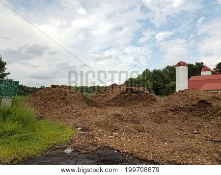 large brown pile of mulch and a silo