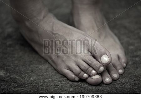 Feet of adult woman on a dark background