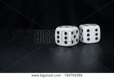 Two gambling dices on a dark table