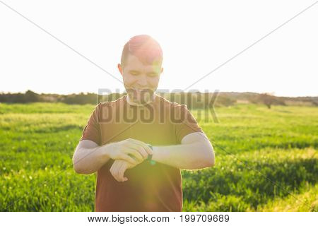 Male runner jogging outside looking at his wearable fitness tracker outside