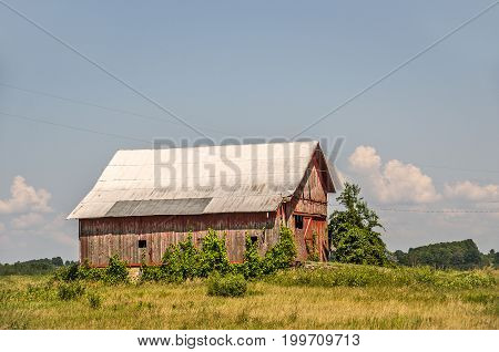 Red barn fading from the sun and weather looks abandoned and in need of some attention