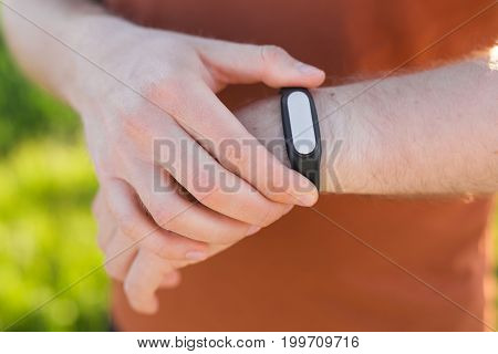 Sportsman checking his pulse on smart watch tracker.