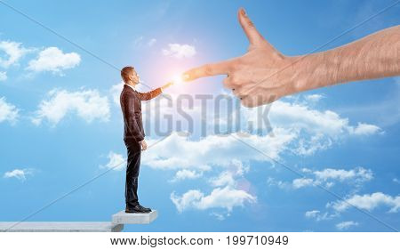 A businessman standing among the clouds to touch fingers with a giant hand. Business angel. Unexpected assistance. Financial help.