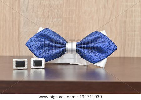 Wedding ceremony accesories details. Cuff-links and blue bow tie